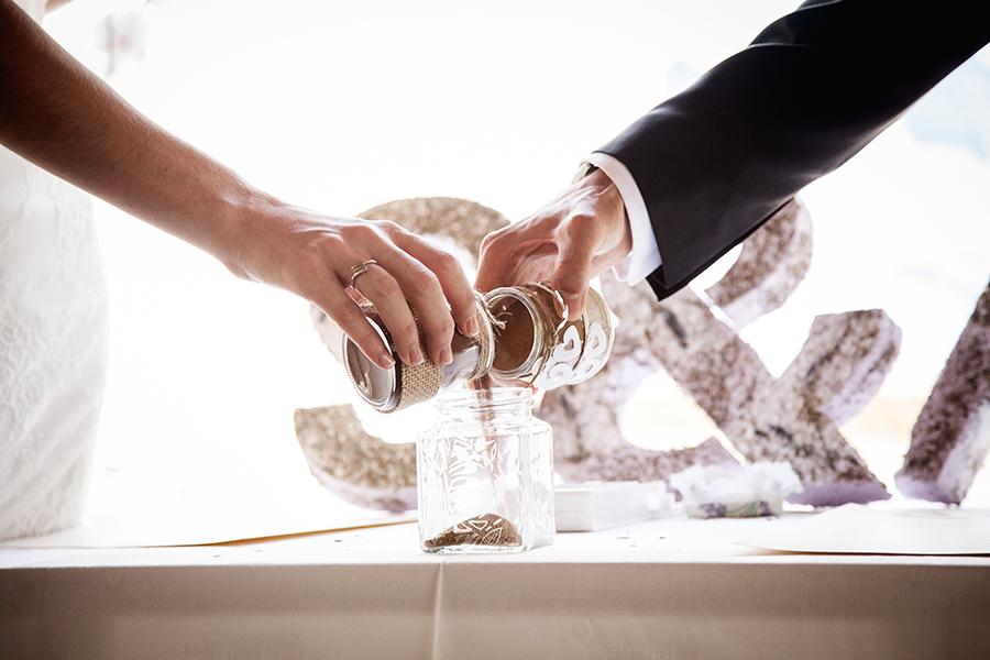Fotografía del momento de la ceremonia de la arena en el reportaje de boda